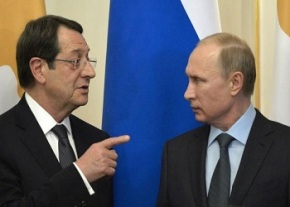 Cyprus President Nicos Anastasiades speaks to Russian President Vladimir Putin during their meeting at the Novo-Ogaryovo state residence outside Moscow